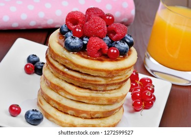 Delicious pancakes with berries in a plate and orange juice on wooden table