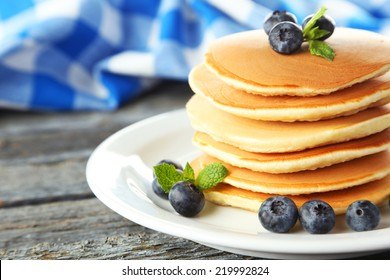 Delicious pancakes with blueberries on blue wooden background