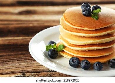 Delicious pancakes with blueberries on brown wooden background