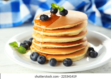 Delicious pancakes with blueberries on white wooden background