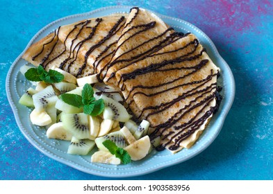Delicious pancakes for breakfast with fruit and chocolate