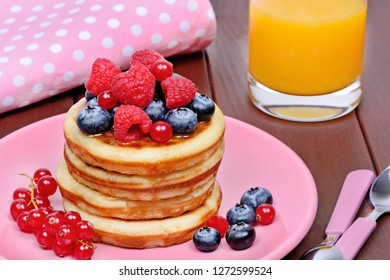 Delicious pancakes with fresh berries in a pink plate and orange juice on table