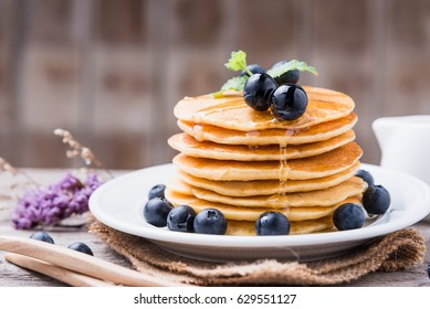 Delicious pancakes with fresh blueberries and honey on wood back