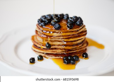 Delicious pancakes with fresh blueberries and maple syrup. Selective focus