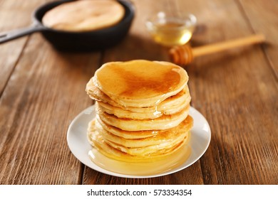 Delicious pancakes with maple syrup on wooden table