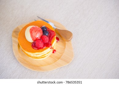 Delicious pancakes with strawberry on table background.