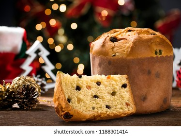 Delicious Panettone slice with candied fruits with blinking blurred christmas lights.