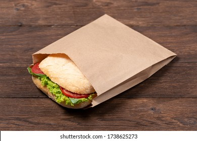 delicious panini in paper bag on wooden background. concept of eco packages of recyclables. still life