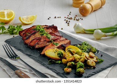 Delicious pan-seared steak with vegetables on a stone board. Meat meal with brussels sprouts, potatoes, onions and herb butter on a white wooden table.