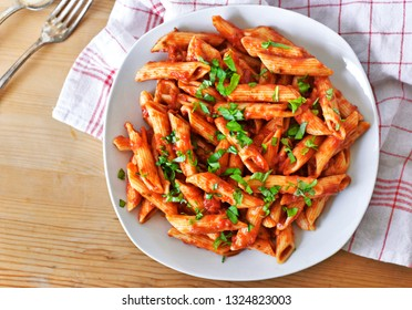 Delicious pasta dish with fresh basil on a wooden table. Top view scene, healthy eating or healthy lifestyle. Penne napoli or pasta arrabiata, closeup shot.