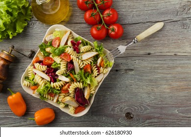 Delicious pasta salad with green lettuce, tomatoes and roasted chicken.