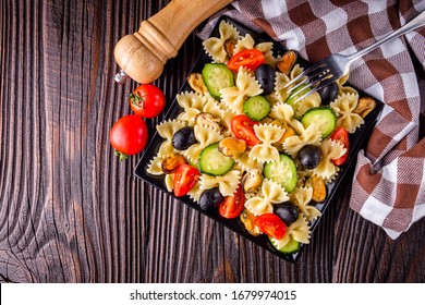 Delicious pasta salad with tomato cucumber and olives on wooden rustic background