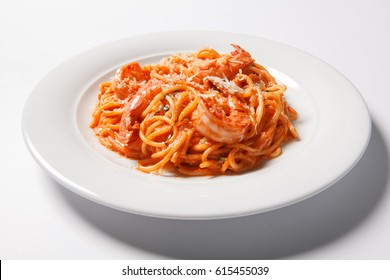 Delicious pasta spaghetti with shrimps, tomato sauce, cheese on a white plate. Isolated