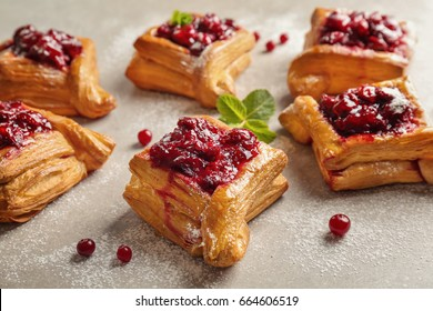Delicious pastries with cherry jam on light background