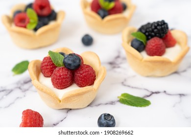 Delicious pastry mini fruit cream cheese pies or tart cakes with fresh raspberry, blueberry and blackberry