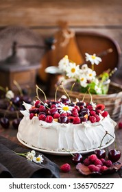 Delicious Pavlova meringue cake decorated with fresh raspberries and cherries on rustic background