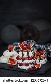 Delicious Pavlova meringue cakes decorated with chocolate cream, fresh figs and raspberries on dark background