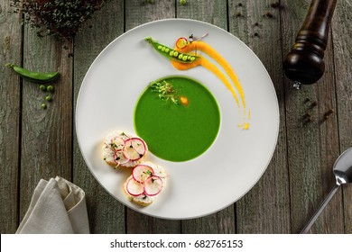 Delicious pea cream soup in a rim soup plate. Healthy traditional European cuisine food on a table.