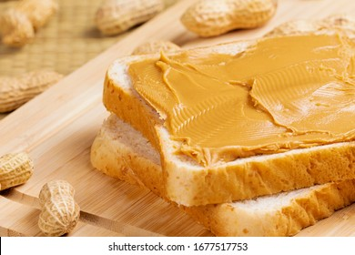 Delicious peanut butter sandwich on a wooden background with peanuts