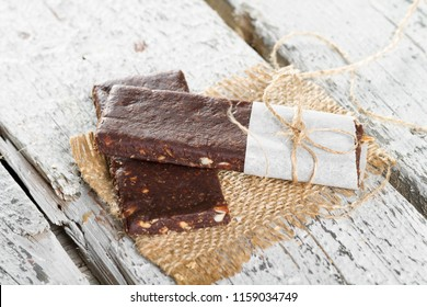 Delicious Peanut Chocolate Bar made with Date Fruit, Cocoa Mass, Oatmeal, Himalayan Salt, Chicory Root and Fiber serving at burlap cloth on rustic white wood background. Copy space for text area.