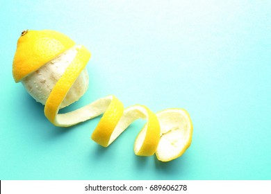 Delicious peeled lemon on color background