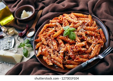 delicious penne arrabiata on a clay plate with fresh basil and grated pecorino cheese on a rustic table with brown cloth, fork and garetd cheese, view from above, close-up