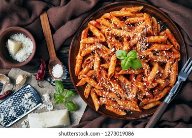 delicious penne arrabiata on an earthenware plate with fresh basil and grated pecorino cheese on a rustic table with brown cloth, fork and ingredients, view from above, flatlay, close-up