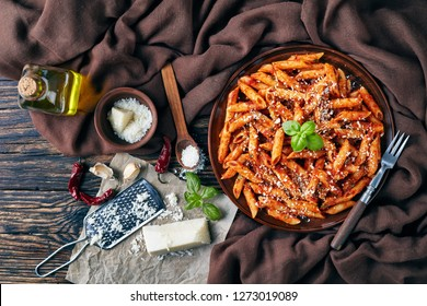 delicious penne arrabiata on an earthenware plate with fresh basil and grated pecorino cheese on a rustic table with brown cloth, fork and ingredients, view from above, flatlay