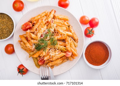 delicious penne pasta on wood white table. tasty italian dinner.top view