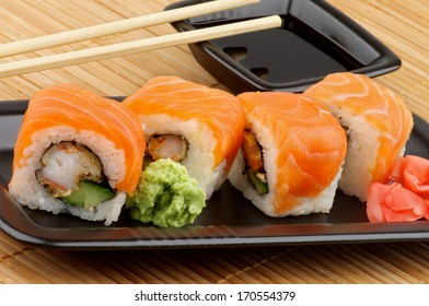 Delicious Philadelphia Sushi with Wasabi, Marinated Ginger and Soy Sauce in Black Square Shape Bowl with Pair of Chopsticks on Straw mat background