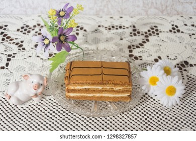 Delicious piece of chocolate cake by flowers  and decorative pig.