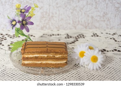 """Delicious piece of chocolate cake """"Ideal"""" with decorative flowers  on a crystal vase"""