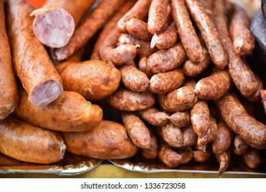 Delicious pieces of smoked sausage exposed for sale in the market. Selective focus and small depth of field