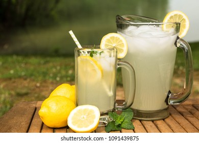 Delicious pitcher and glass of lemonade next to an outdoor lake on a wood table in summer