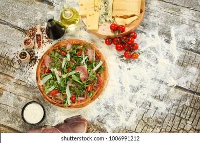 Delicious pizza with arugula, cheese tomato and bacon