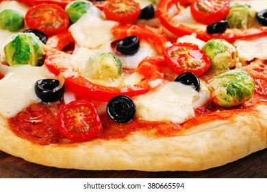 Delicious pizza with cheese and vegetables on wooden cutting board closeup