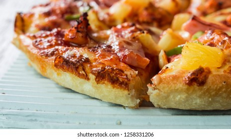 Delicious Pizza delivery in a cardboard with Onion, Olive, Pepperoni, Mozzarella, Green Pepper on wooden background. Close-up, Selective focus.
