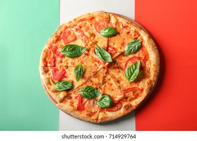Delicious pizza with fresh basil on Italian flag on background