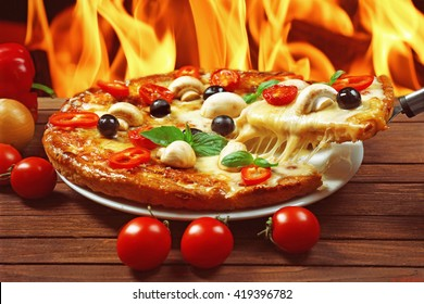 Delicious pizza and fresh vegetables on fire flame background