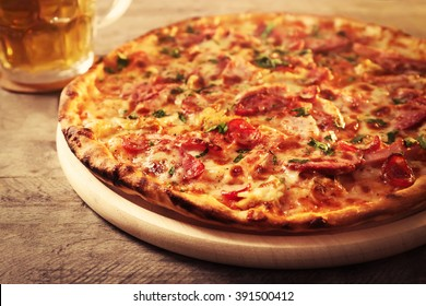Delicious pizza  and glass of beer are on wooden table, close up