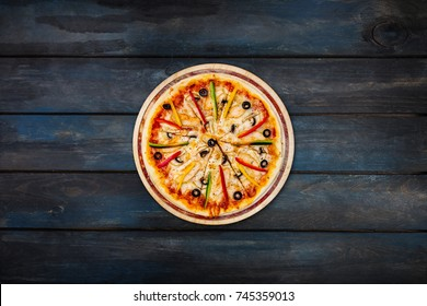 Delicious pizza with mushrooms chicken sweet peppers and olives on a dark wooden background. Top view center orientation