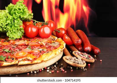 delicious pizza, salami, tomatoes and spices on wooden table on flame background
