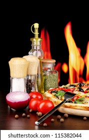 Delicious pizza with spices on wooden table on fire background