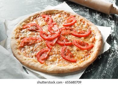 Delicious pizza with tomato on dark background