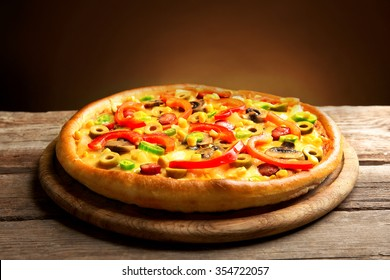 Delicious pizza with vegetables on brown background