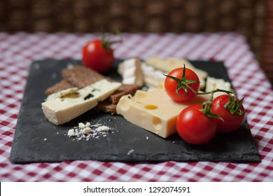 Delicious plate of french cheese served with fresh ripe tomatoes and bread on a black charcoal board. Red and white tablecloth for a picnic mood