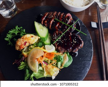 A delicious plate of modern Asian fusion steak with a salad and dumpling with chopsticks and rice to the side.