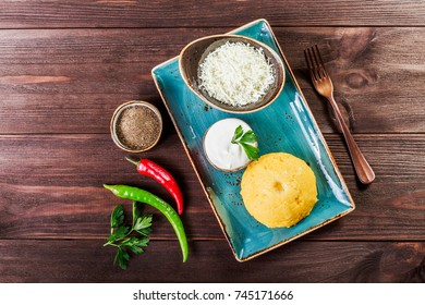 Delicious polenta - Corn porridge hominy with goat cheese, butter and sour cream on wooden background. Healthy food. Top view
