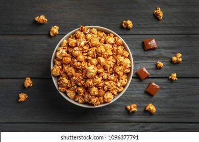 Delicious popcorn with caramel in bowl and candies on wooden background, top view