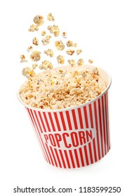 Delicious popcorn falling into red paper bucket on white background